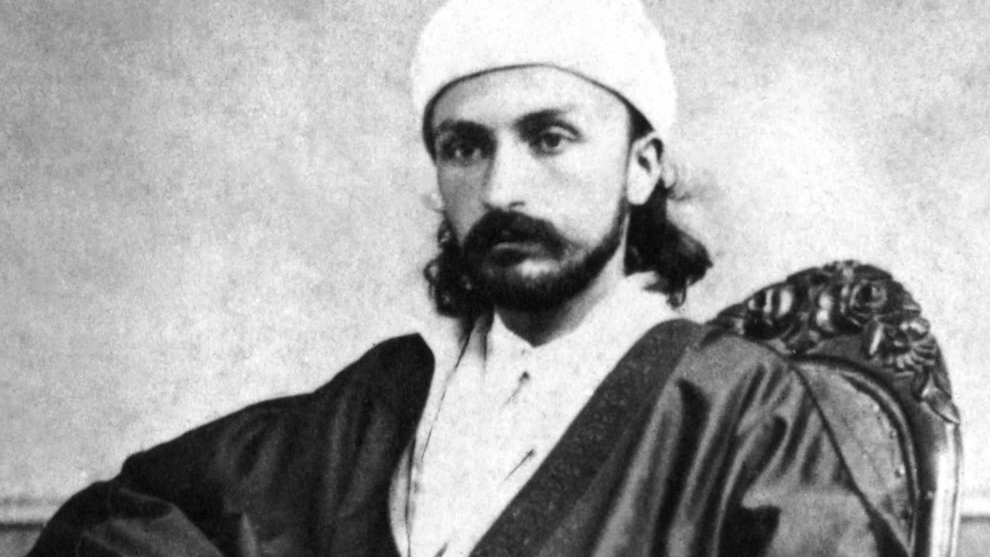 'Abdu'l-Bahá, as a young man, seated in a chair for an official portrait