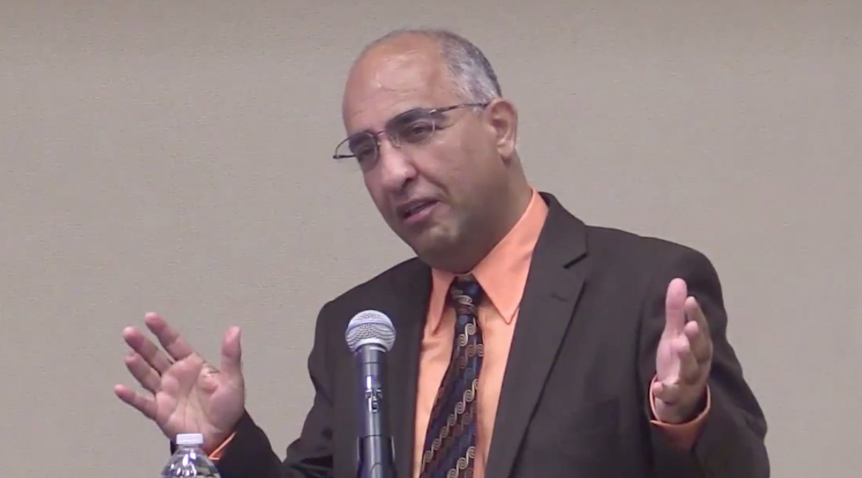 Habib Riazati speaking at a lectern and gestering animatedly with both hands