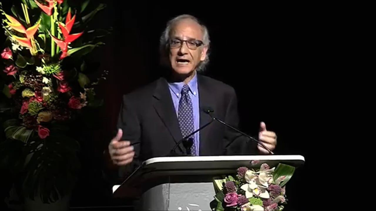 Nader Saiedi talks at a lectern where boquets of flowers are arranged